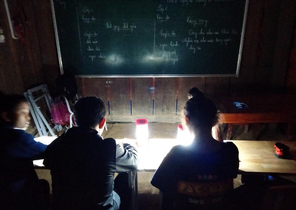 Học sinh lớp ghép bản Đoòng ôn bài bên ánh đèn sạc. Ảnh: Việt Anh.