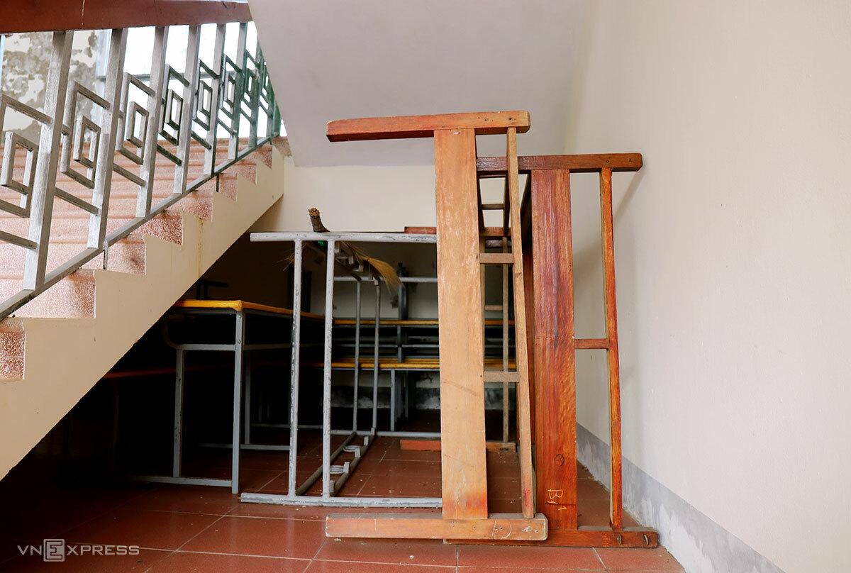 Bàn ghế không sử dụng được gom lại một chỗ đặt dưới cầu thang dãy phòng học hai tầng. Ảnh: Đức Hùng