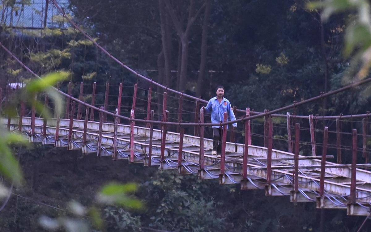 Một người đàn ông băng qua cây cầu hư hỏng lúc chiều tối. Theo người dân địa phương, mỗi ngày vẫn có hàng chục học sinh, người lao động cố băng qua đây để tiết kiệm thời gian. Ảnh: Lê Hoàng.