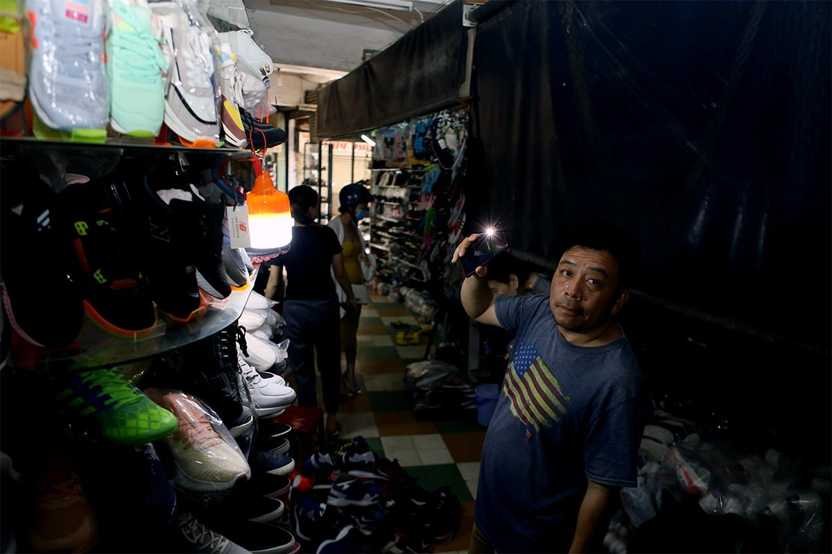 Tiểu thương chợ Đầm Nha Trang chong đèn để kinh doanh sau khi bị cắt điện nước, ngày 22/1. Ảnh: Xuân Ngọc.