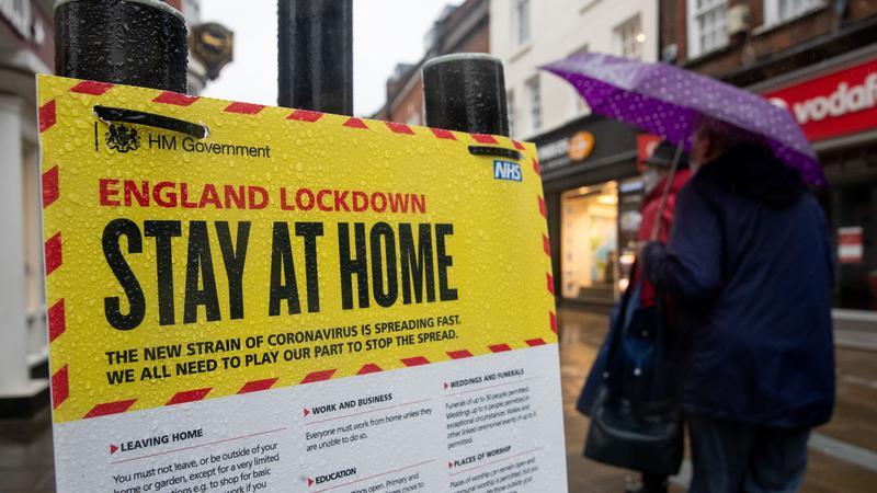Người dân đi qua bảng khuyến cáo ở nhà tránh Covid-19 trên đường phố Winchester, Anh. Ảnh: PA.