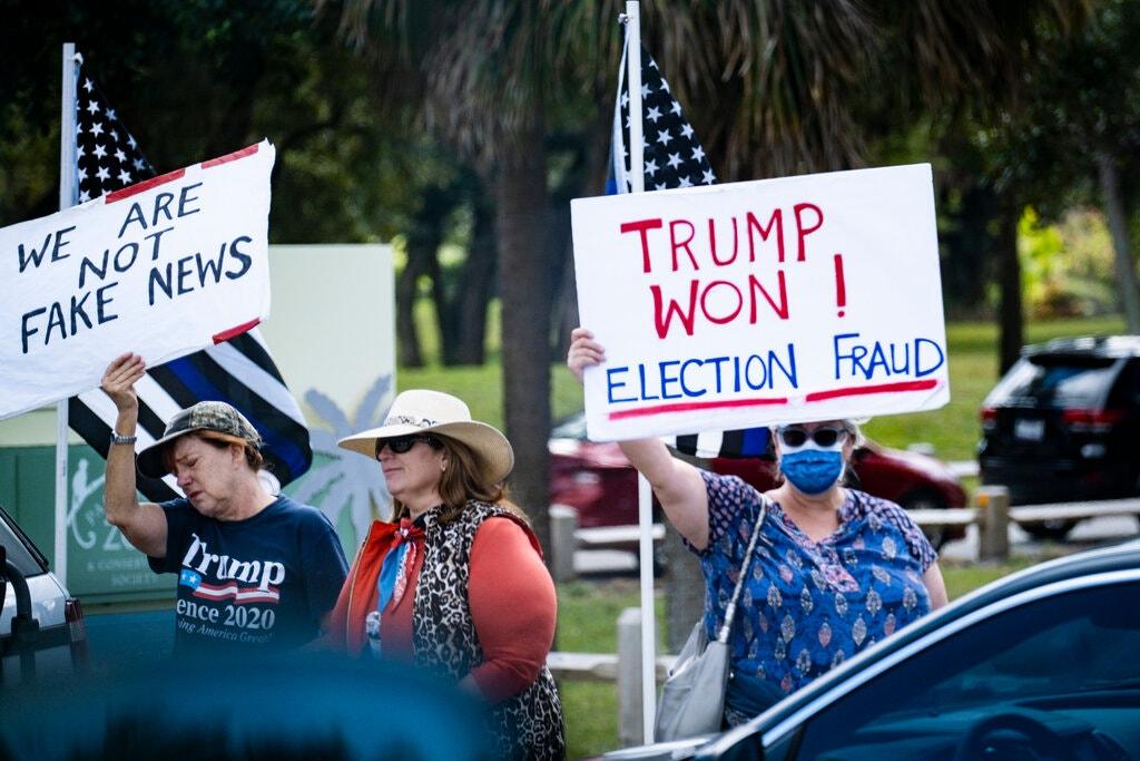 Người ủng hộ Trump giơ biển có dòng chữ Trump thắng! Gian lận bầu cử và Chúng tôi không phải là tin giả khi đoàn xe chở ông đi qua tại Florida ngày 20/1. Ảnh: NYTimes.