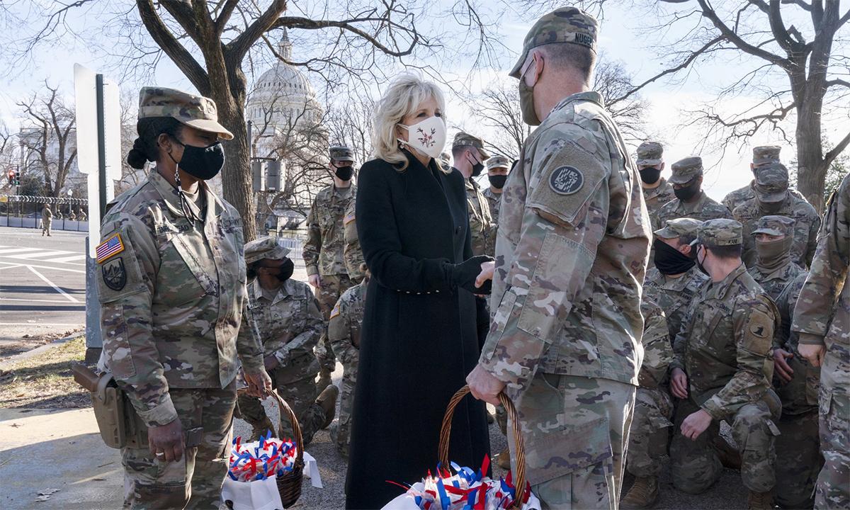 Đệ nhất Phu nhân Jill Biden (mặc đồ đen, đứng giữa) bắt tay một binh sĩ Vệ binh Quốc gia Mỹ bên ngoài tòa nhà Quốc hội sau khi phát bánh quy, ngày 22/1. Ảnh: AP.