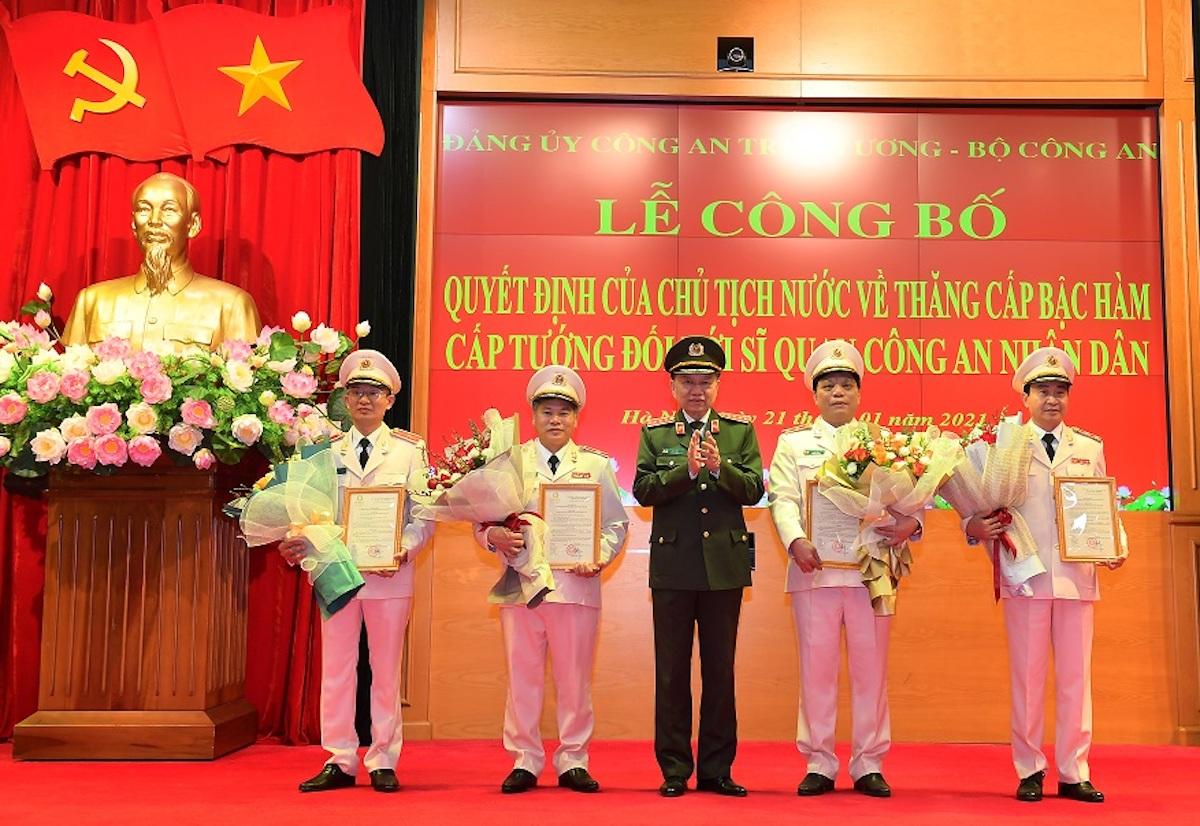 Bộ trưởng Công an Tô Lâm (giữa) trao quyết định và tặng hoa chúc mừng các tướng lĩnh được thăng cấp bậc hàm. Ảnh: Công an Hà Nội