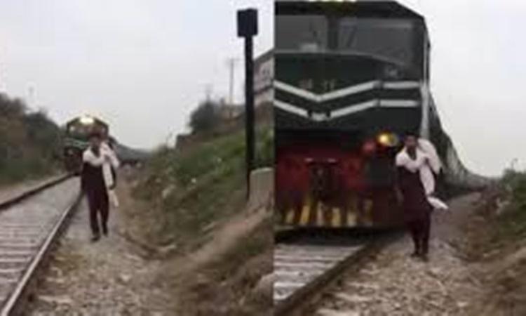 Hình ảnh Hamza Naveed đi trên đường ray hôm 22/1, phía sau là đoàn tàu đang tiến gần. Ảnh: Bolnews.