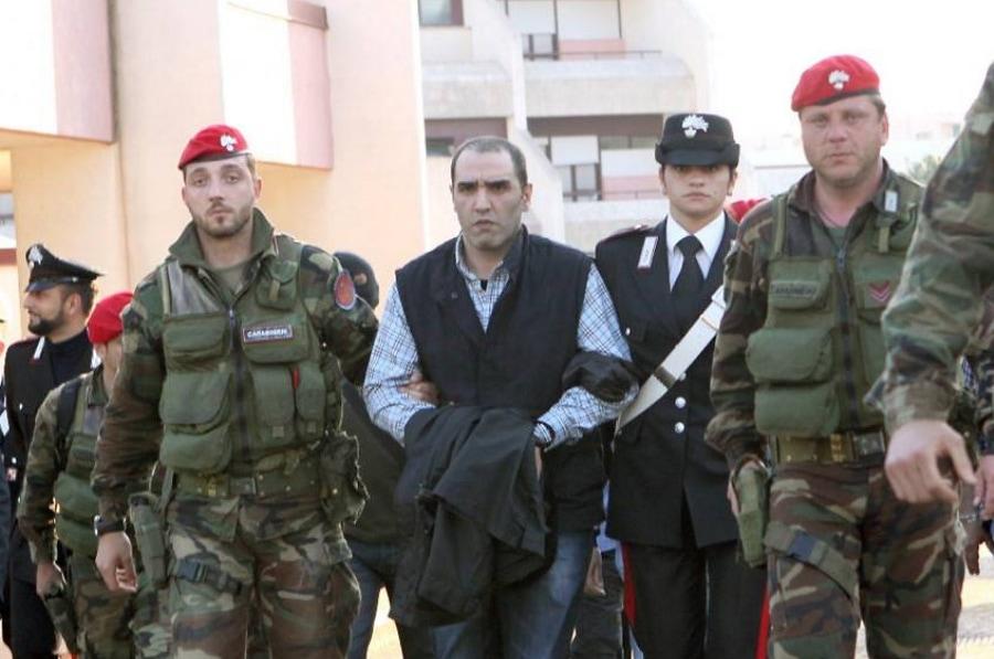 Salvatore Coluccio, kẻ ghi là thủ lĩnh gia đình mafia 'Ndrangheta, bị cảnh sát dẫn giải sau khi bị bắt giữ vào tháng 5/2009. Ảnh: AFP.