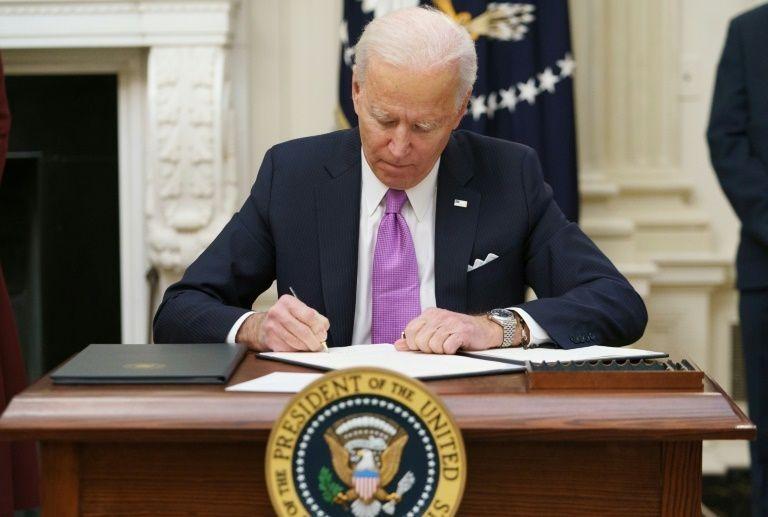 Tổng thống Joe Biden ký sắc lệnh trong ngày đầu nhậm chức hôm 20/1 tại Nhà Trắng. Ảnh: AFP