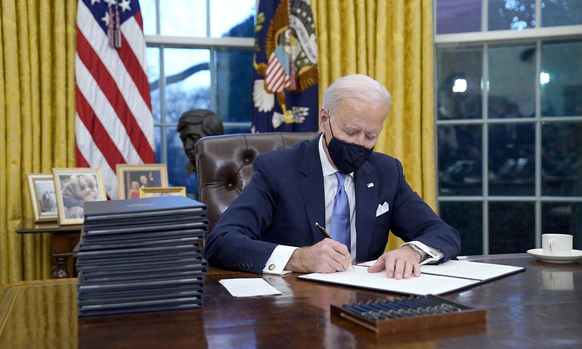 Tổng thống Mỹ Joe Biden ký sắc lệnh tại Phòng Bầu dục ở Nhà Trắng hôm 20/1. Ảnh: AP.
