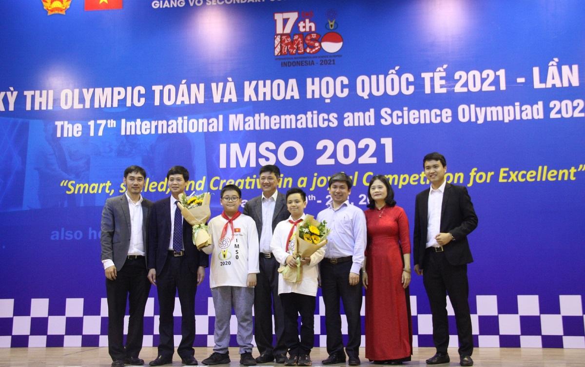 Đại diện Sở Giáo dục và Đào tạo Hà Nội tặng hoa chúc mừng hai học sinh giành huy chương vàng. Ảnh: Giáo dục và Thời đại.