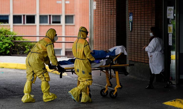 Nhân viên y tế di chuyển bệnh nhân Covid-19 tại khu vực chăm sóc đặc biệt ở bệnh viện gần Madrid, Tây Ban Nha tháng 4/2020. Ảnh: Reuters.