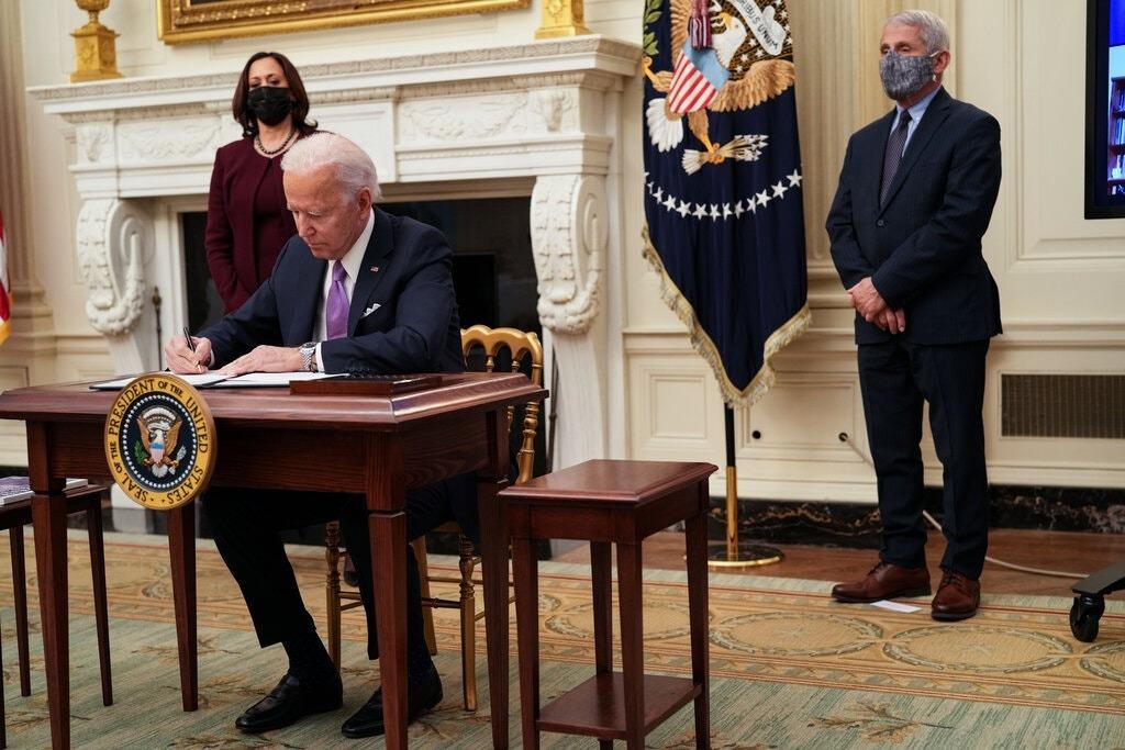 Tổng thống Mỹ Joe Biden ký một loạt sắc lệnh nhằm tăng cường phản ứng của liên bang đối với Covid-19 tại Nhà Trắng hôm 21/1. Ảnh: The New York Times.