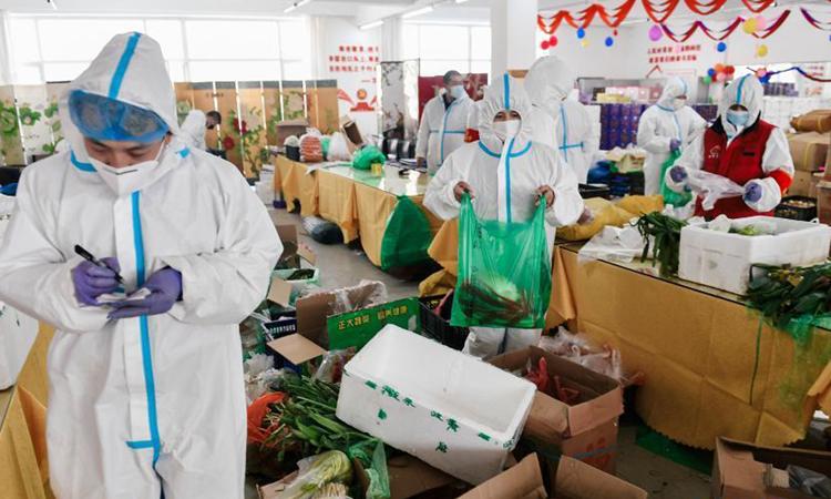 Nhóm nhân viên chuẩn bị nhu yếu phẩm hàng ngày cho người dân thành phố Thông Hóa, tỉnh Cát Lâm, đông bắc Trung Quốc hôm 24/1. Ảnh: Xinhua.
