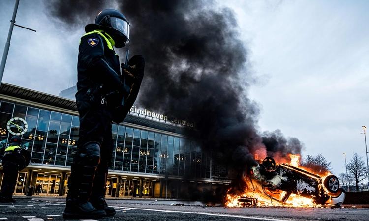 Cảnh sát đứng cạnh một chiếc xe ô tô bị người biểu tình thiêu rụi ở Eindhoven, Hà Lan, hôm 24/1. Ảnh: AFP.