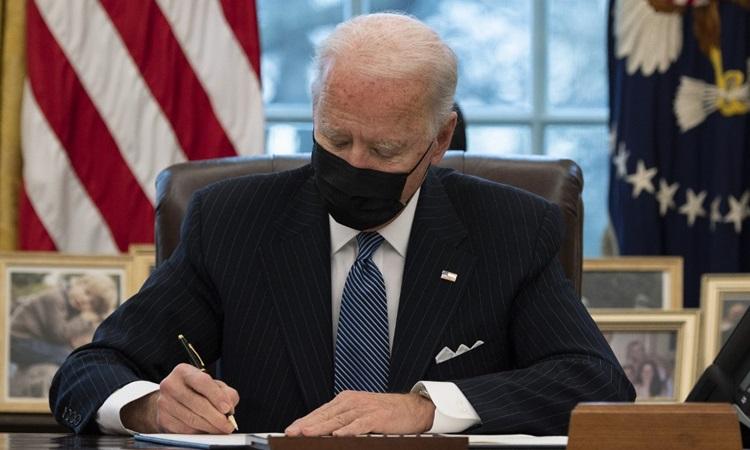 Tổng thống Mỹ Joe Biden ký sắc lệnh tại Nhà Trắng hôm 25/1. Ảnh: AFP.