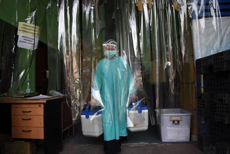 Nhân viên y tế Indonesia vận chuyển các thùng chứa vaccine Sinovac. Ảnh: AFP.