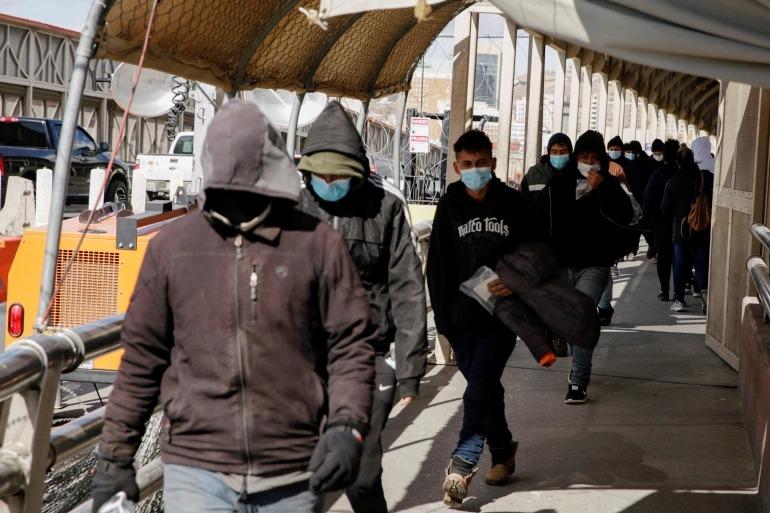 Người nhập cư bị trục xuất khỏi Mỹ đi về hướng Mexico tại cầu biên giới Paso del Norte. Ảnh: Reuters