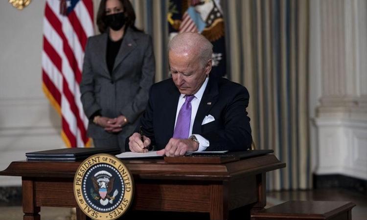 Tổng thống Mỹ Joe Biden ký sắc lệnh trong Nhà Trắng hôm 26/1. Ảnh: AFP.