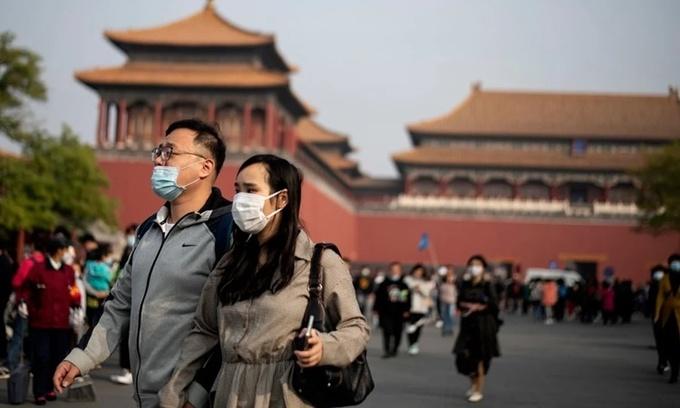 Người dân đeo khẩu trang bên ngoài Tử Cấm Thành ở thủ đô Bắc Kinh, Trung Quốc, hồi tháng 10. Ảnh: AFP.