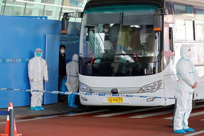 Xe chở nhóm chuyên gia WHO đến điều tra nguồn gốc Covid-19 rời sân bay tại Vũ Hán hôm 14/1. Ảnh: Reuters.