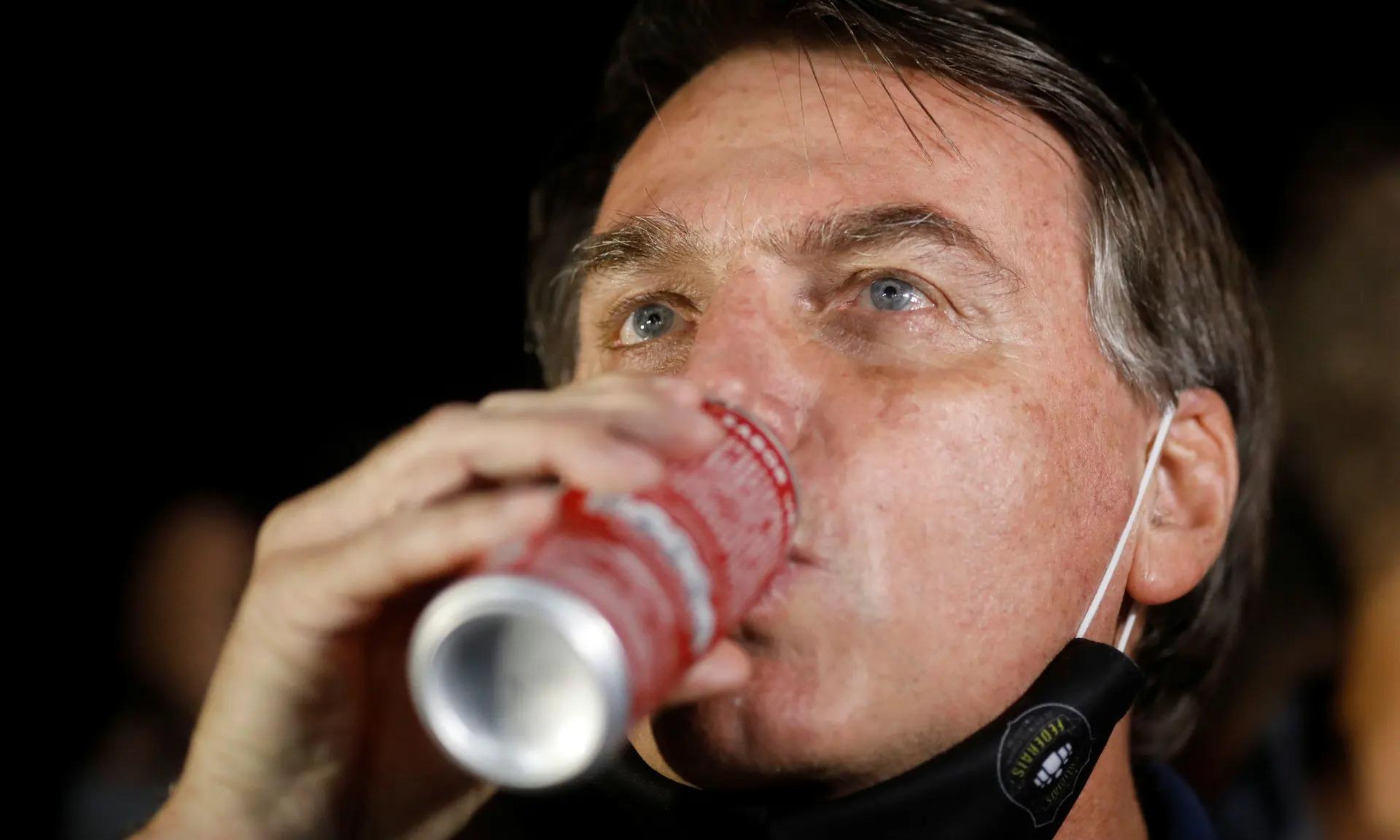 Tổng thống Brazil Bolsonaro uống nước ngọt. Ảnh: Reuters
