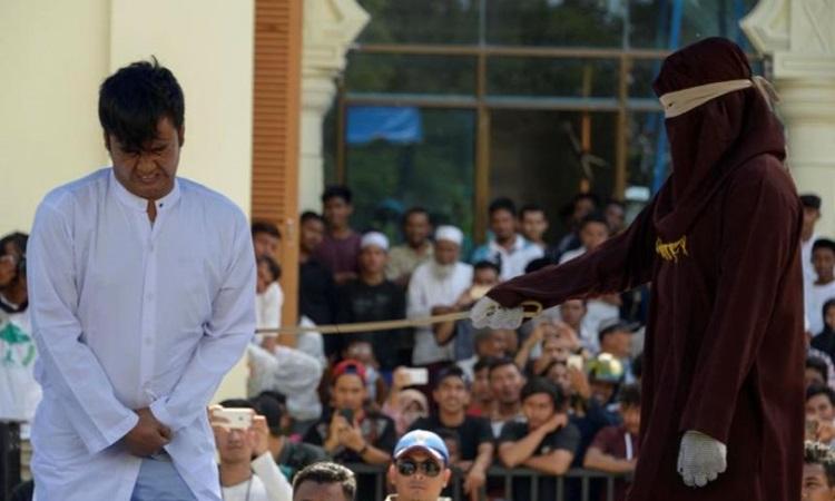 Một người đàn ông ở tỉnh Aceh, Indonesia bị phạt roi công khai vì quan hệ đồng tính hồi năm 2018. Ảnh: AFP.
