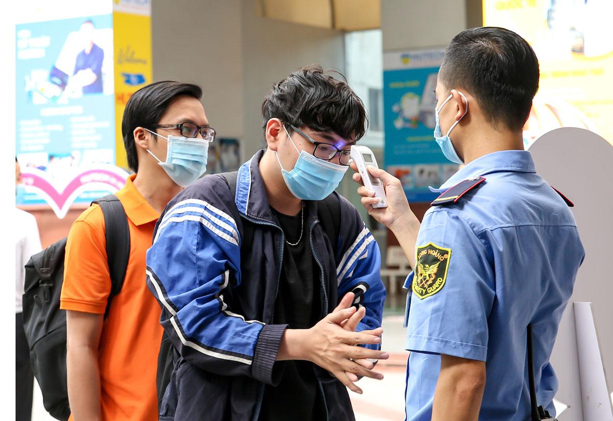 Sinh viên Đại học Công nghệ TP HCM được đo thân nhiệt, rửa tay bằng nước sát khuẩn trước khi vào trường. Ảnh: Mạnh Tùng.