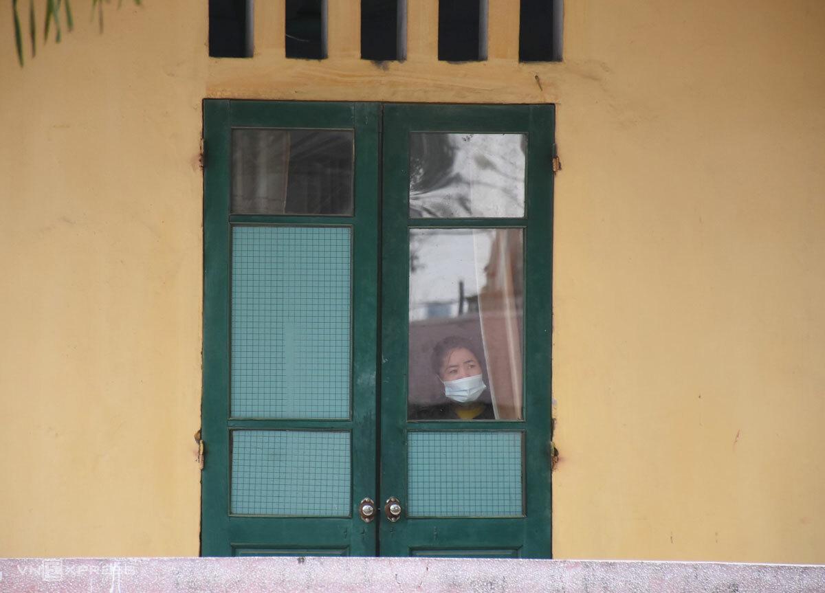 Người trong khu cách ly tập trung qua ô cửa sổ, sáng 30/1. Ảnh: Nguyễn Huệ