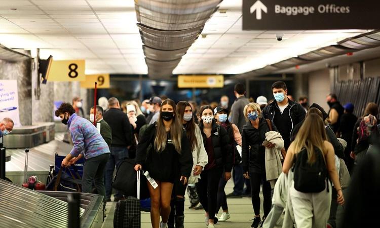 Hành khách đeo khẩu trang trong khu lấy hành lý tại sân bay Denver, Mỹ, hồi tháng 12/2020. Ảnh: Reuters.