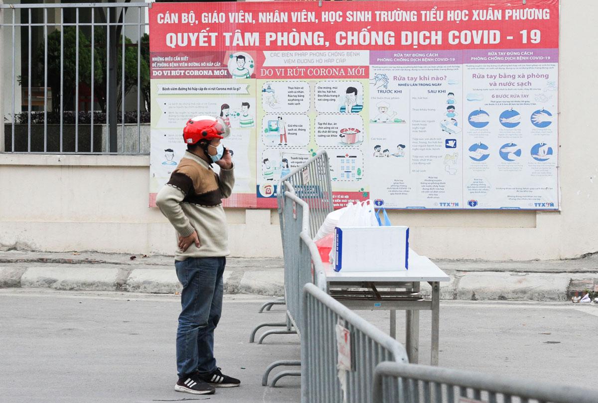 Người thân mang đồ vào cho học sinh trường Tiểu học Xuân Phương diện cách ly sáng 31/1. Ảnh: Báo Giáo dục và Thời đại.