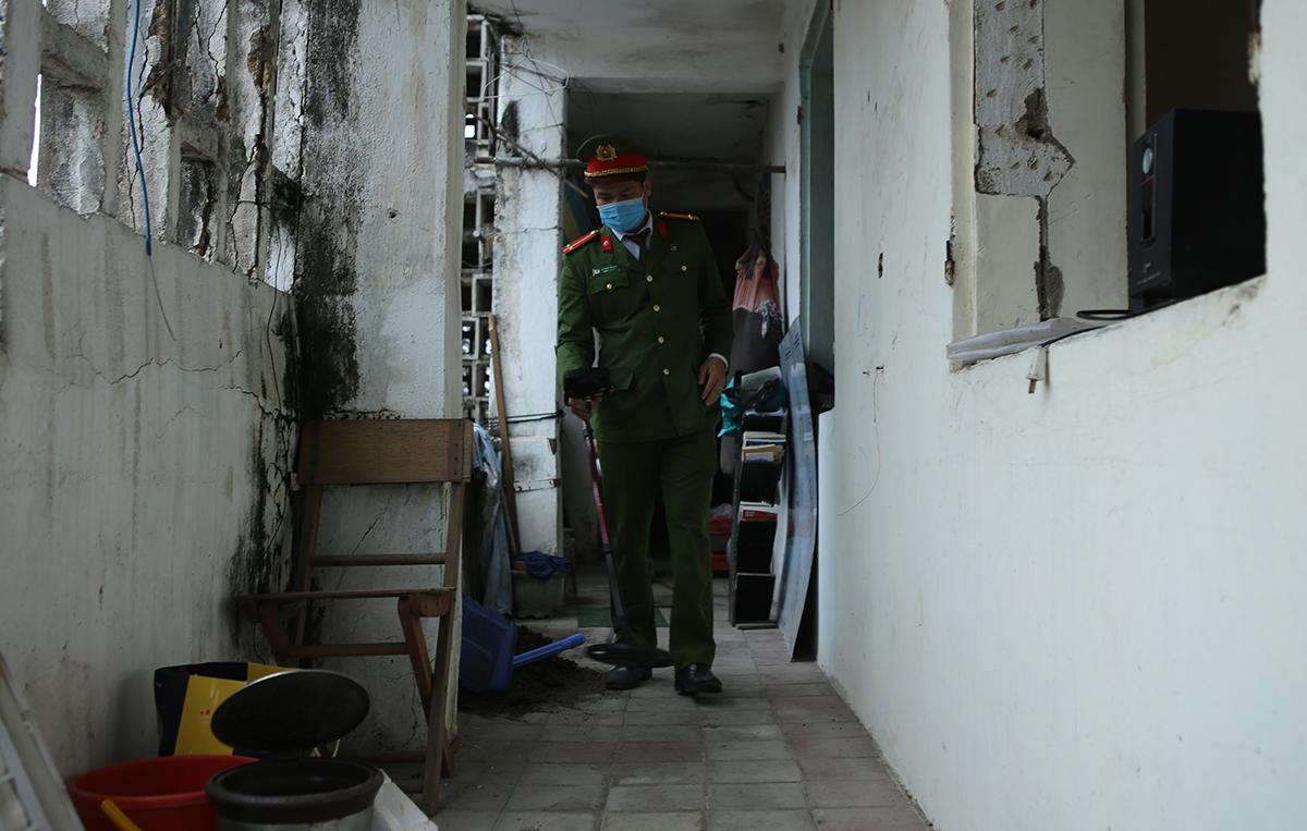 Cán bộ công an dùng thiết bị dò mìn kiểm tra toàn bộ chung cư. Ảnh: Nguyễn Hải