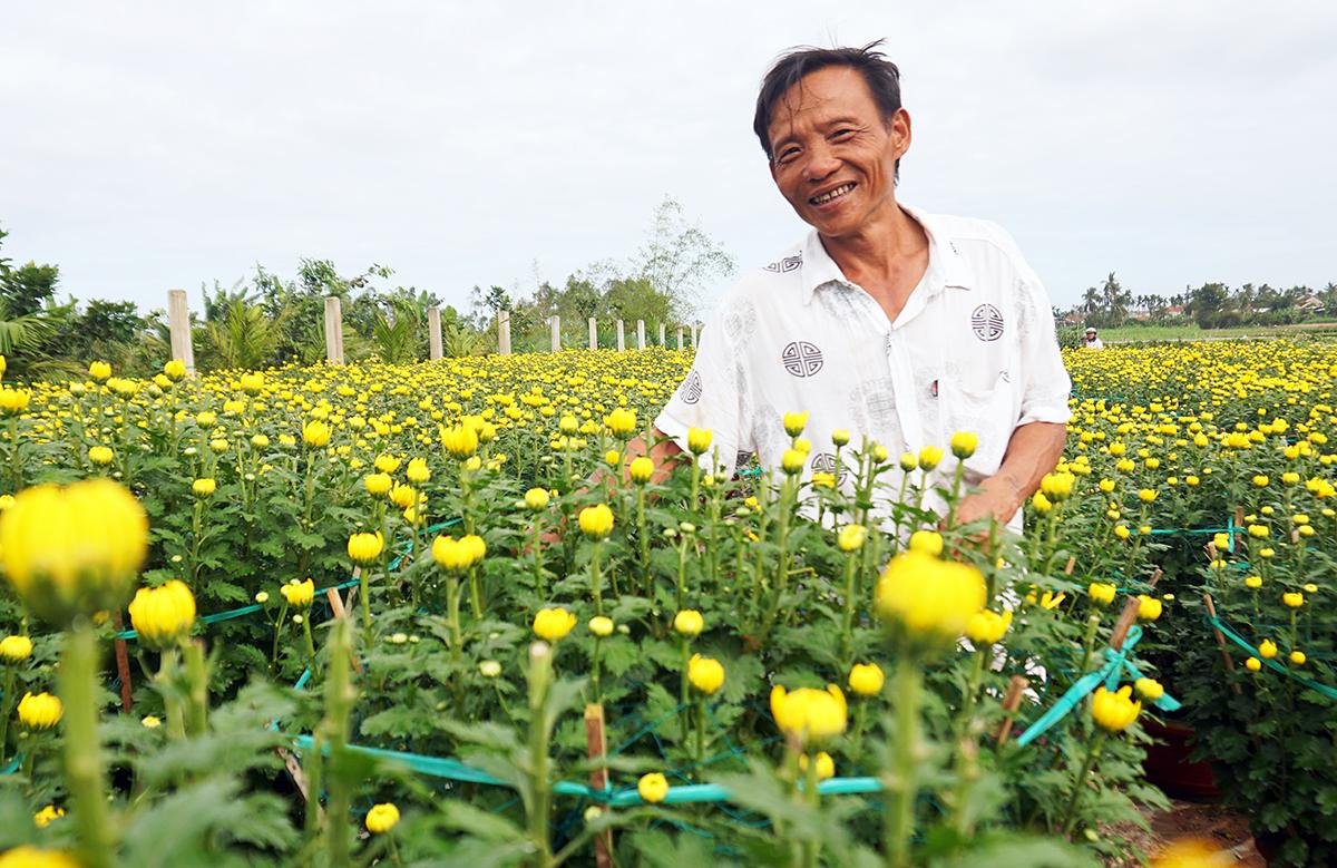Ông Ngọc cười tươi khi nhiều người mua giúp hoa, ủng hộ, chiều 2/2. Ảnh: Phạm Linh.