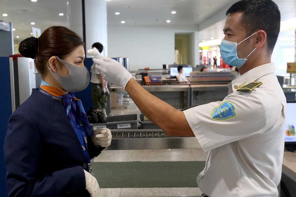 Nhân viên an ninh hàng không kiểm tra thân nhiệt cho tiếp viên. Ảnh: Bá Đô.