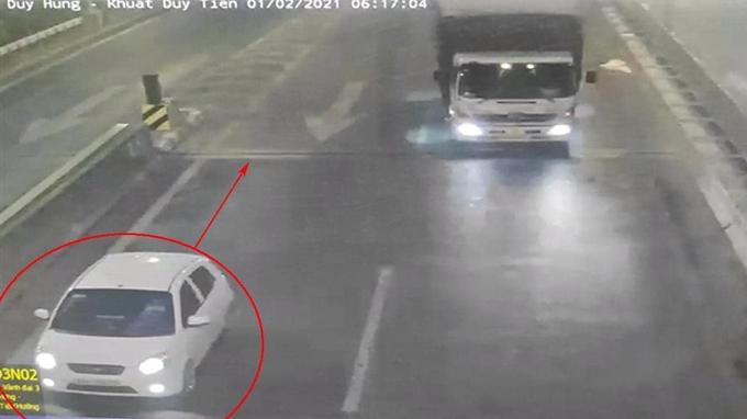 Chiếc xe con màu trắng đi lùi lại lối ra tại đường vành đai ba Hà Nội...