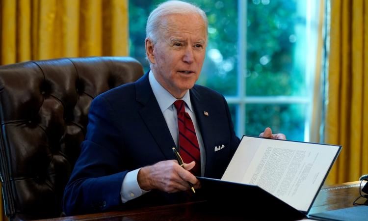 Tổng thống Joe Biden ký sắc lệnh tại Phòng Bầu dục hôm 28/1. Ảnh: AP.
