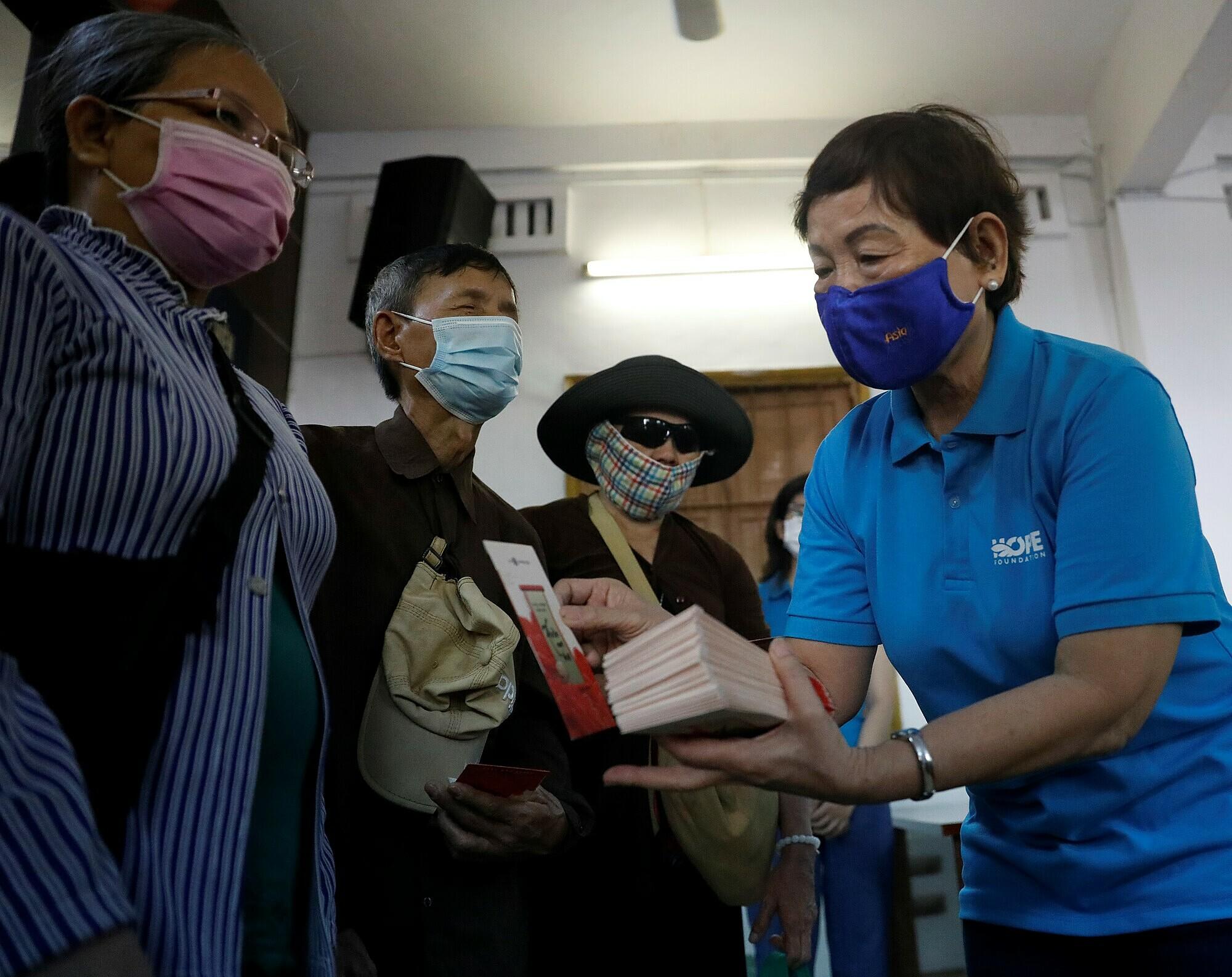 Bà Trương Thanh Thanh trao quà Tết cho người mù nghèo ở TP HCM. Ảnh: Hữu Khoa