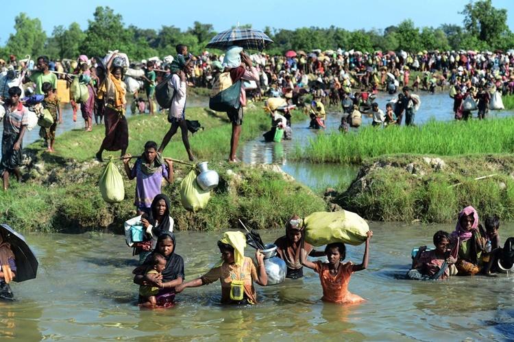Người tị nạn Rohingya lội qua một con kênh cạn để đến Bangladesh sau khi tháo chạy khỏi Myanmar hồi tháng 10/2017. Ảnh: AFP.