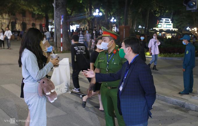 Lực lượng chức năng nhắc nhở người dân đeo khẩu trang ở khu vực hồ Hoàn Kiếm, quận Hoàn Kiếm, Hà Nội, cuối năm 2020. Ảnh: Tất Định