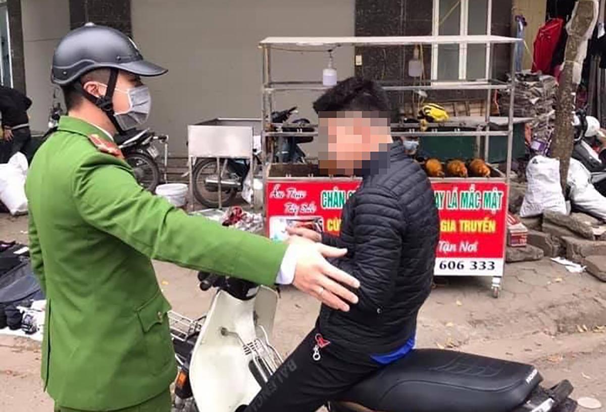 Cảnh sát ra quân xử phạt người không đeo khẩu trang. Ảnh: Phạm Dũng.