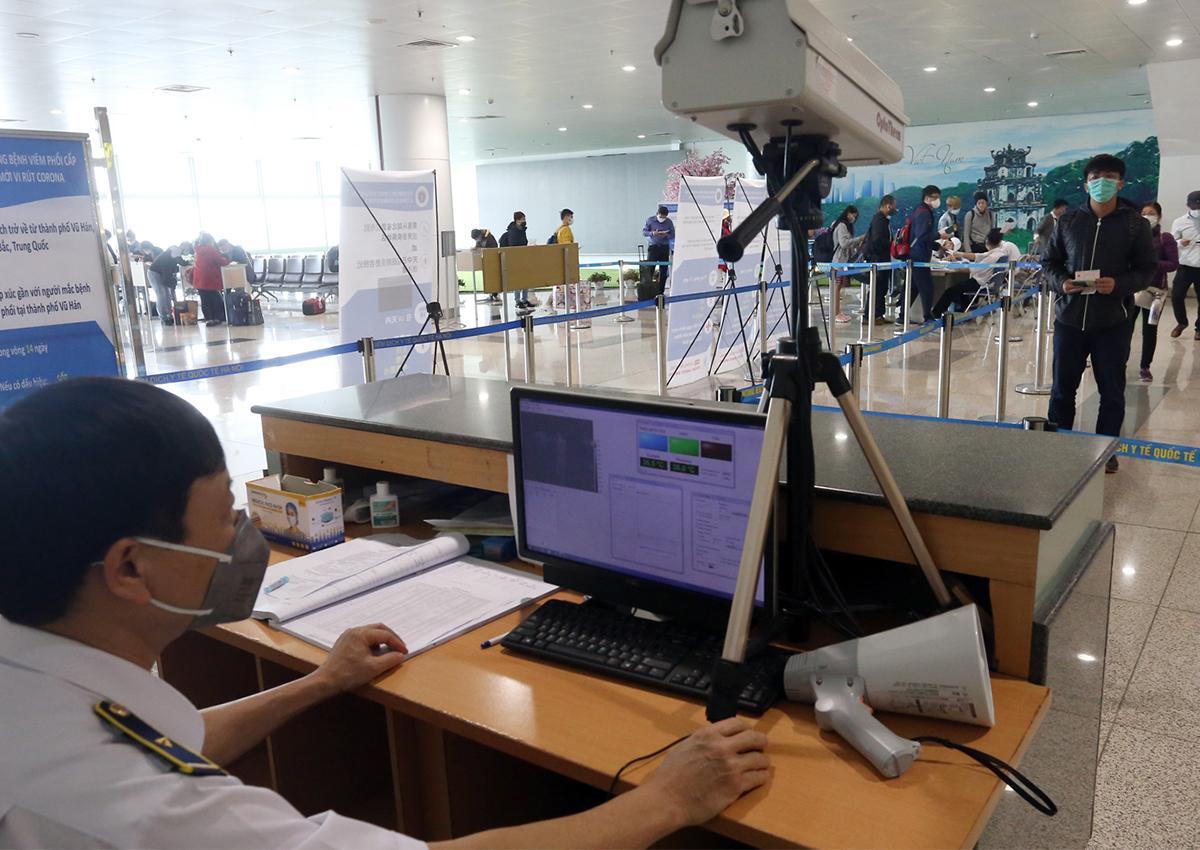 Đo thân nhiệt hành khách ở sân bay Nội Bài. Ảnh: Bá Đô