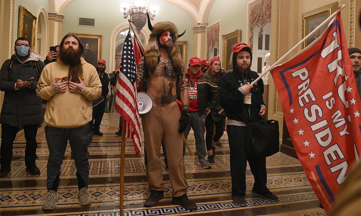 Jacob Chansley (giữa) cùng những người ủng hộ Trump xâm nhập tòa nhà quốc hội Mỹ hôm 6/1. Ảnh: AFP.