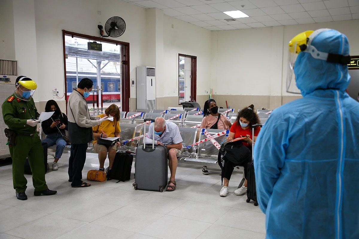 Chuyên viên Sở Ngoại vụ Đà Nẵng cùng lực lượng công an, y tế hướng dẫn khách làm tờ khai y tế tại chốt kiếm soát Ga đường sắt Đà Nẵng, chiều 6/2. Ảnh: Nguyễn Đông.