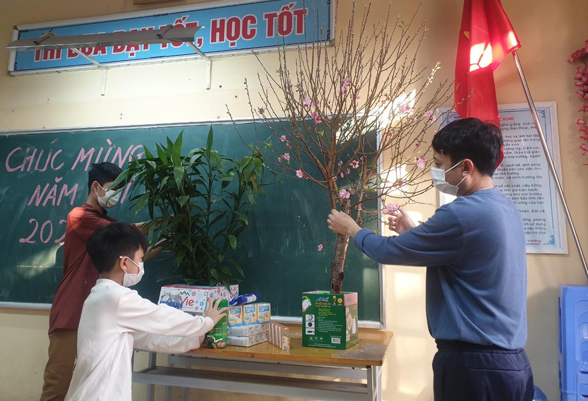 Anh Nguyễn Duy Long cùng hai con trai trang trí phòng cách ly để đón Tết. Ảnh: Nhân vật cung cấp.