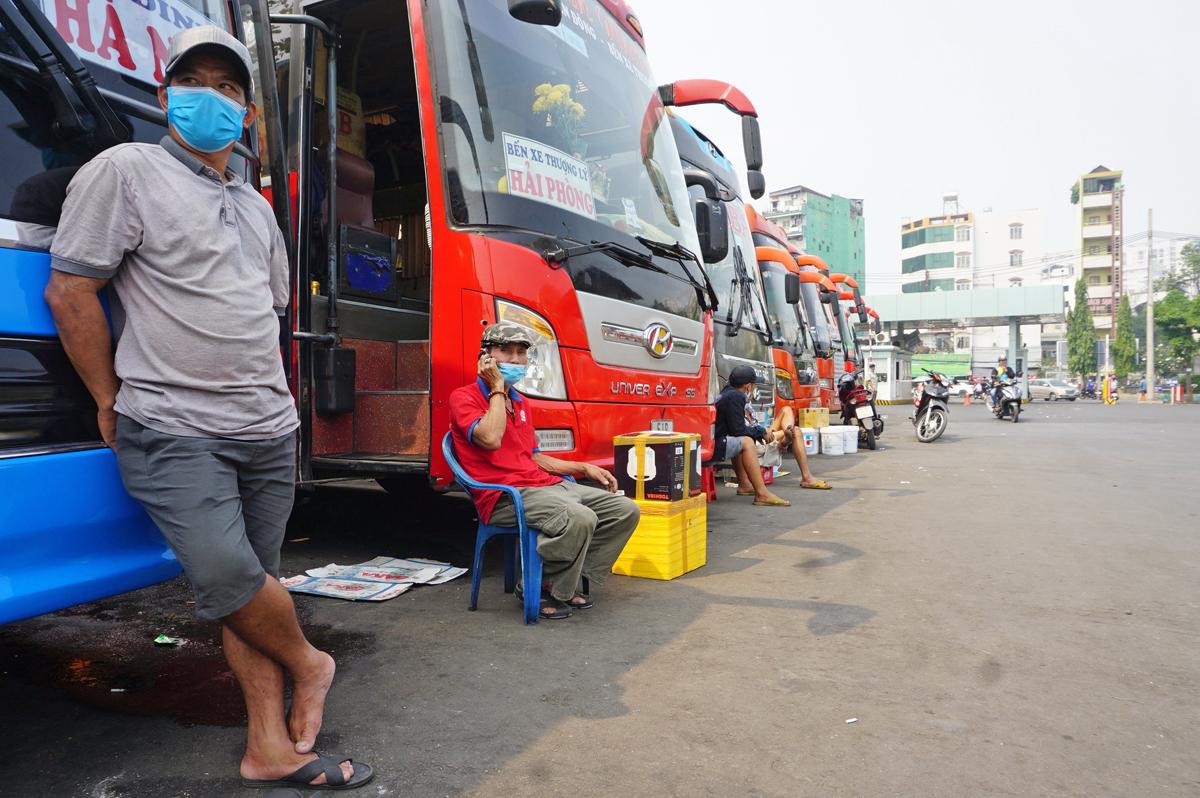 Ông Tây Đô (đứng), chờ khách tại Bến xe Miền Đông về Hải Phòng, trưa 6/2. Ảnh: Gia Minh.