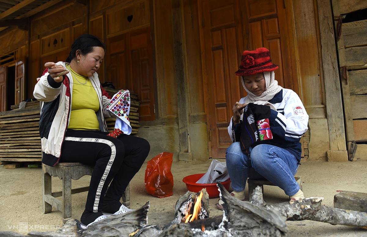 Chị Chẹo Thị Náy (bên phải) ngồi sưởi lửa thêu váy cùng người thím. Ảnh: Lê Hoàng.