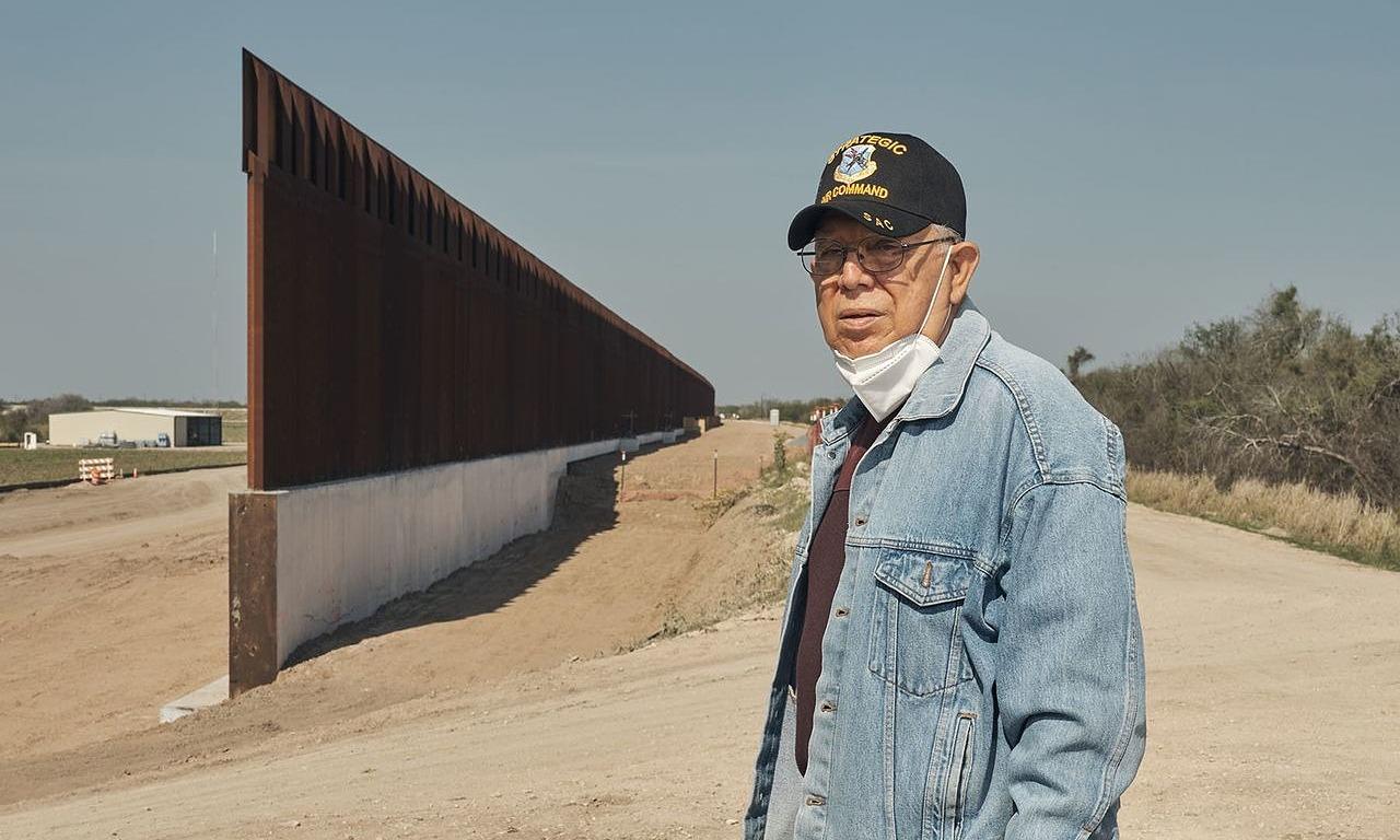 Reynaldo Anzaldua đứng ở ranh giới khu đất của nhà mình, gần bức tường biên giới tại Mission, Texas ngày 3/4. Ảnh: WSJ.