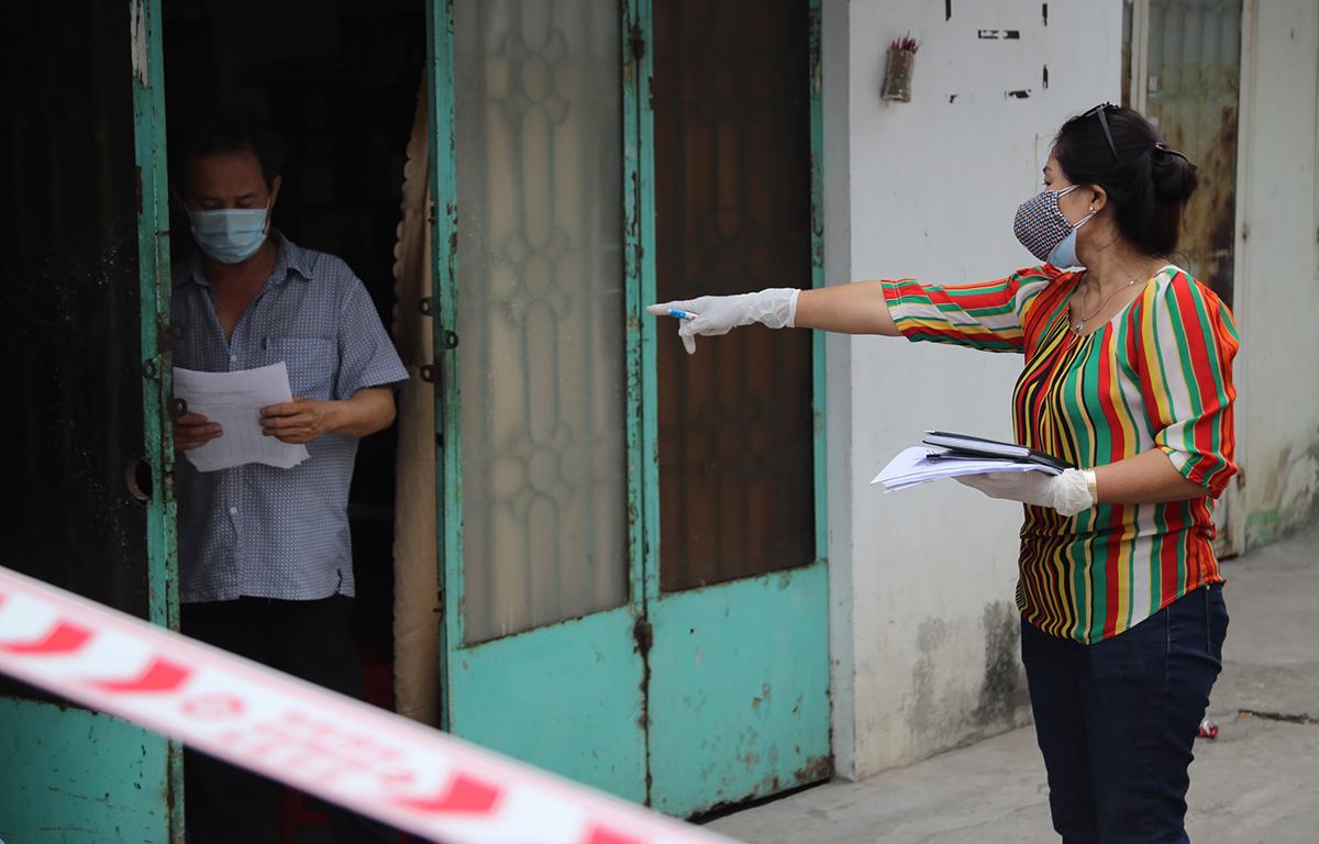 Nhân viên trung tâm y tế quận 12 đến từng hộ dân trong khu phong tỏa ở phường Thạnh Lộc, quận 12, để đưa giấy khai báo y tế, sáng 8/2. Ảnh: Đình Văn.