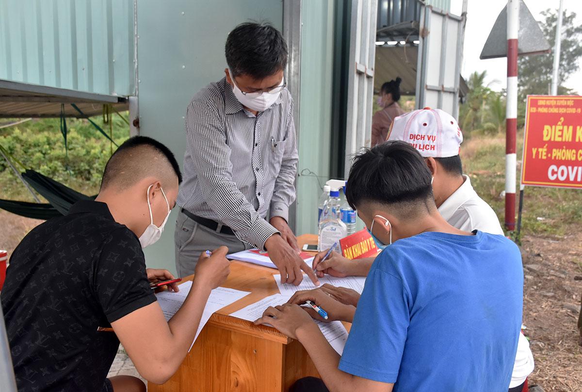 Người đi đường khai báo y tế tại chốt trên quốc lộ 55 ở huyện Xuyên Mộc, chiều 10/2. Ảnh: Huế Thương.