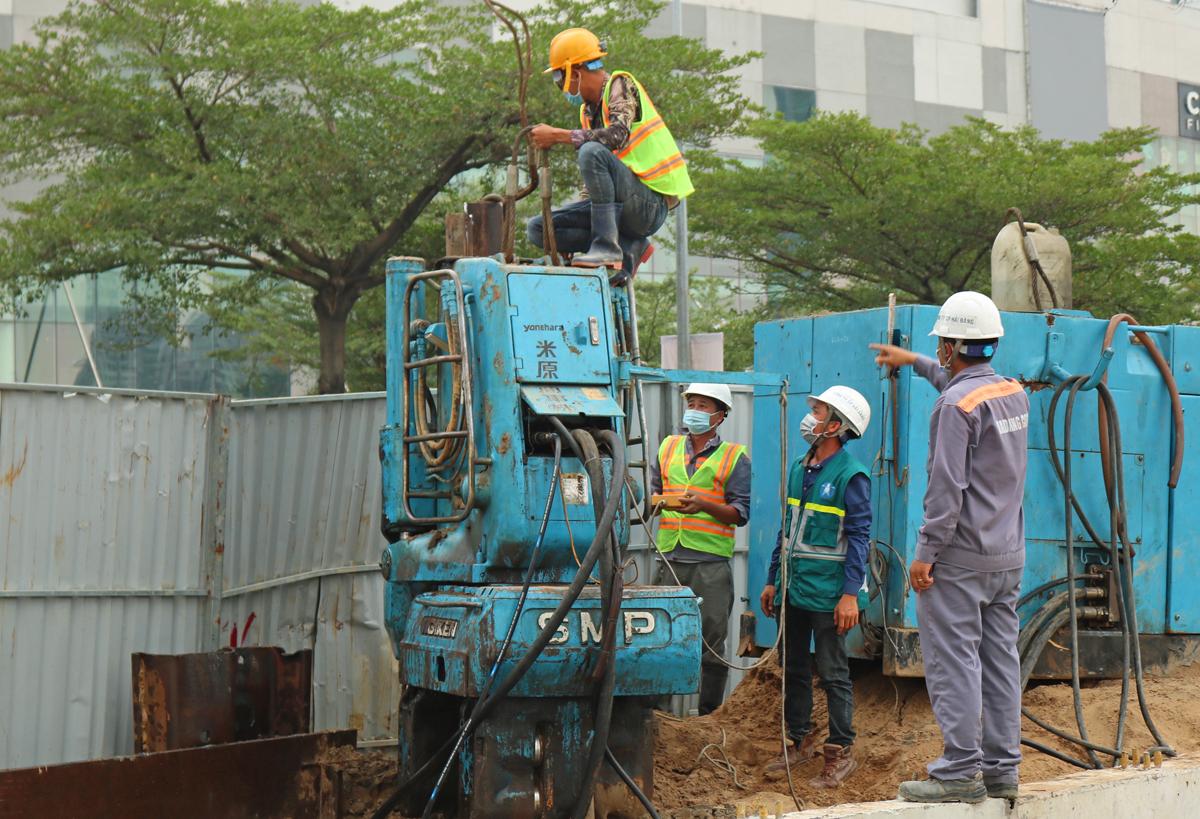 Công nhân xử lý máy khoan tại công trình hầm chui Nguyễn Văn Linh - Nguyễn Hữu Thọ, chiều 29 Tết. Ảnh: Gia Minh.