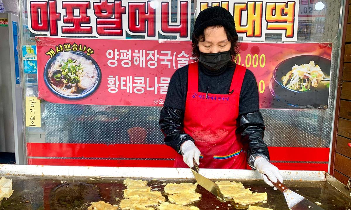 Lee Soon-ai làm bánh kếp truyền thống tại cửa hàng của mình ở thủ đô Seoul, Hàn Quốc, ngày 11/2. Ảnh: Reuters.