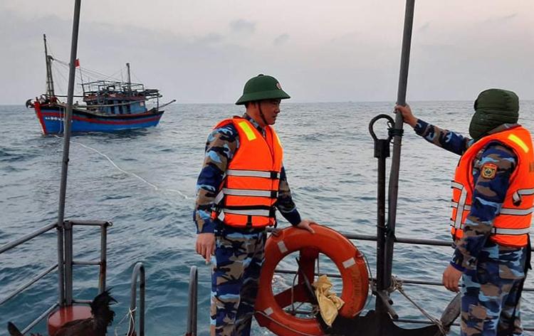 Trung tá Trần Ngọc Tú (bên trái) cùng đồng đội trong một lần ra khơi cứu hộ tàu gặp nạn. Ảnh: Biên phòng